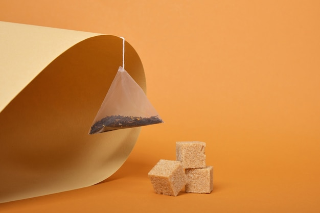 Pyramid shaped tea bag and cane sugar cubes on brown rolled paper background, copy space color trend
