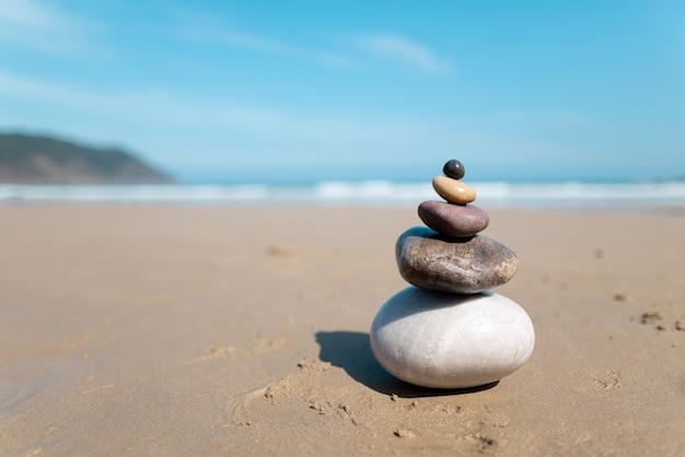 Pyramid of stones for meditation lying on sea coast.