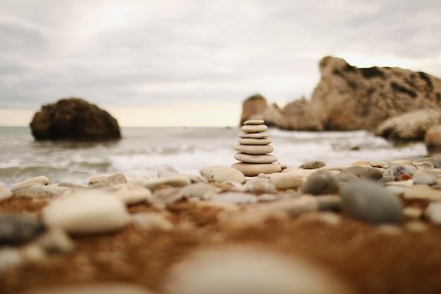 푸른 바다 배경에 화창한 날에 해변에 피라미드 돌