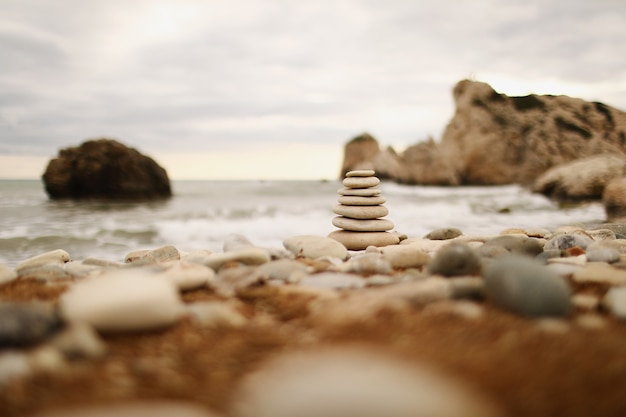 Pyramid stones on the seashore on a sunny day on the blue sea background