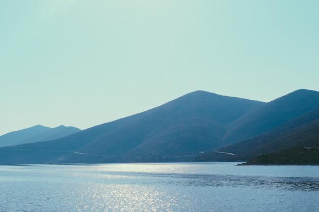 Пирамидальная горная цепь через побережье эгейского моря в греции. пейзаж, который сочетает в себе горы, море, голубое небо и солнечный свет. дорога через горную цепь.