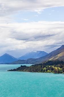 Пирамидальные горы и заснеженные вершины на берегу озера вакатипу южный остров новая зеландия