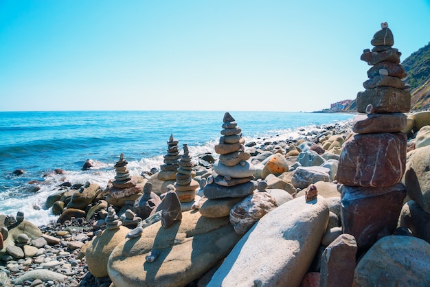 Pyramids of stones on the beach with the bright sun. crimea.