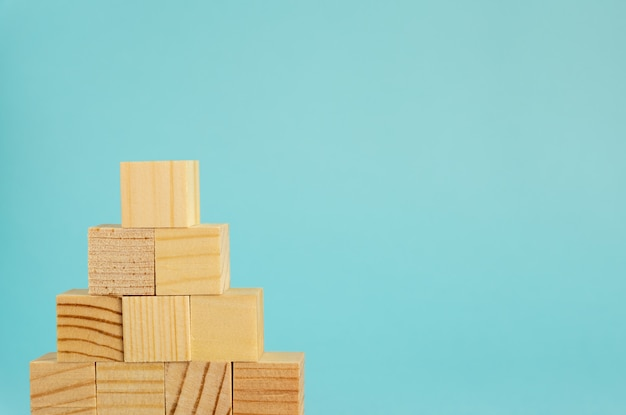 Pyremid construction made of wooden cubes on blue background with copy space. mockup composition for design