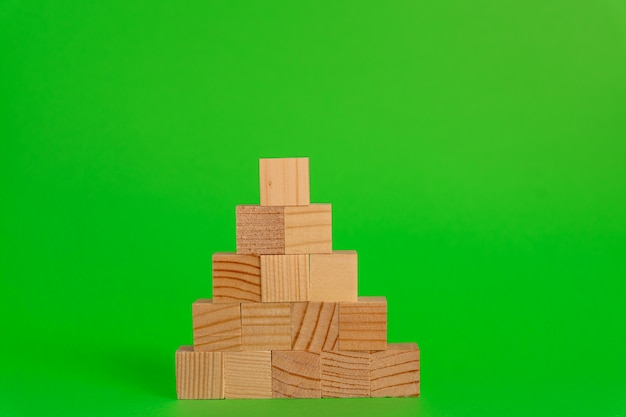 Pyremid construction made of wooden cubes on green background with copy space. mockup composition for design