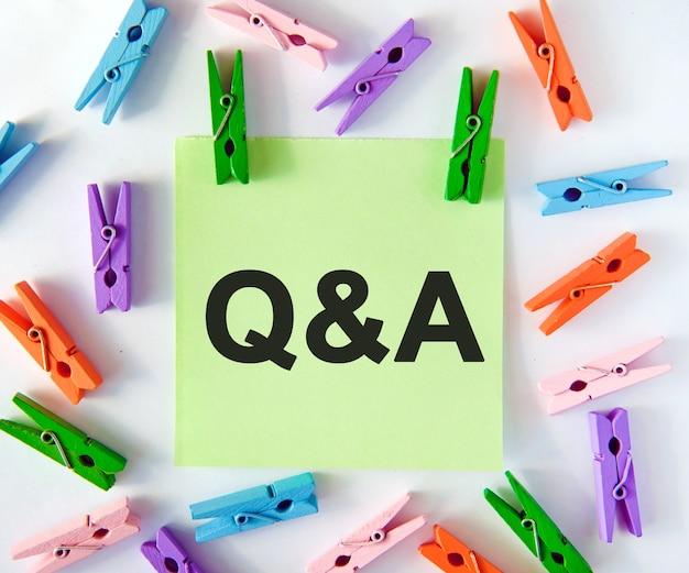 Q&aの質問は、マルチカラーの洗濯バサミが付いた緑色のステッカーで回答されます Premium写真