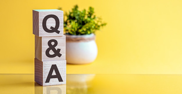 복사 공간, 비즈니스 개념 노란색 배경에 나무 큐브로 만든 qa 단어