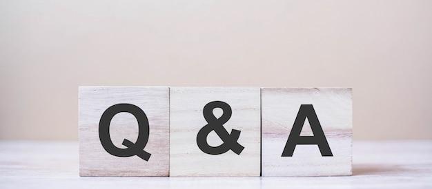 Q & a слово с деревянным кубическим блоком.