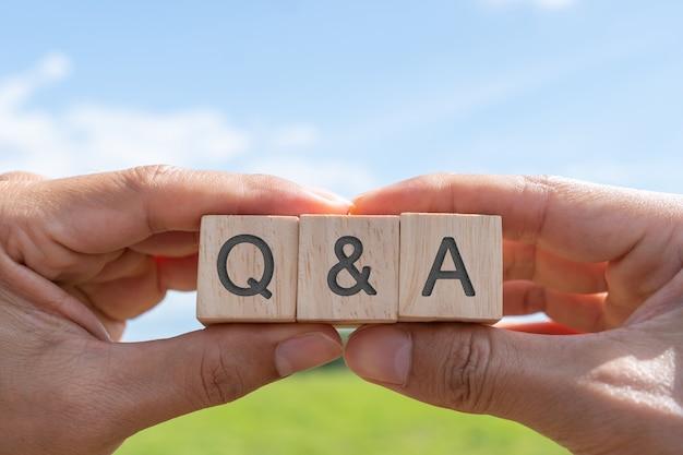 Q и алфавит на деревянном кубе в руке с фоном. вопрос и ответ значение концепции.