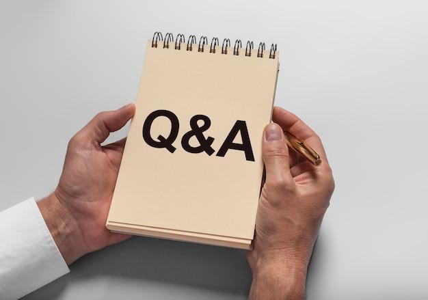 Концепция q. надпись qa, аббревиатура на блокноте. вопросы и ответы о бизнесе.