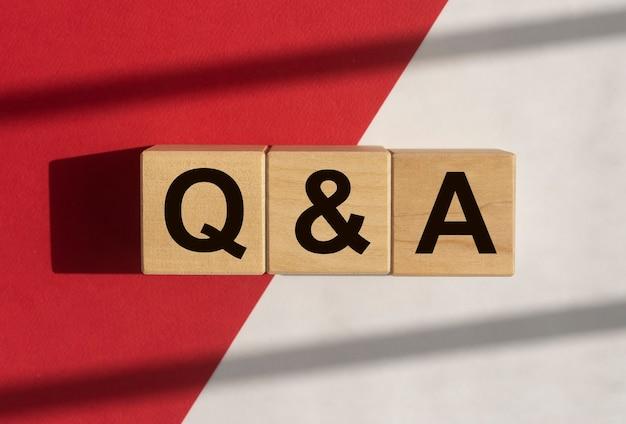 白と赤の背景にqaテキスト。 qnaの頭字語。 qコンセプト。質問と回答。