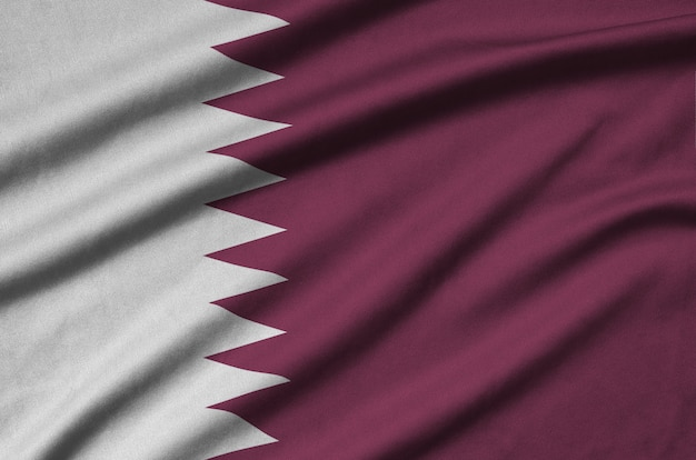 Qatar flag  is depicted on a sports cloth fabric with many folds.
