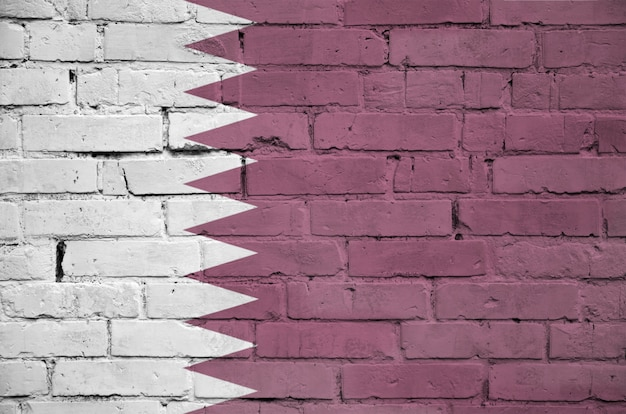 Qatar flag is painted onto an old brick wall