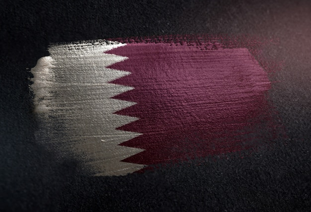Qatar flag made of metallic brush paint on grunge dark wall