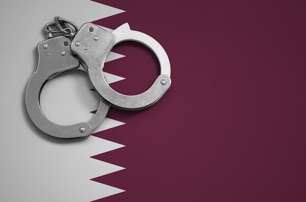 Qatar flag  and police handcuffs. the concept of crime and offenses in the country