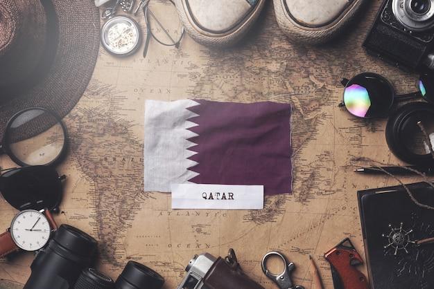 Qatar flag between traveler's accessories on old vintage map. overhead shot