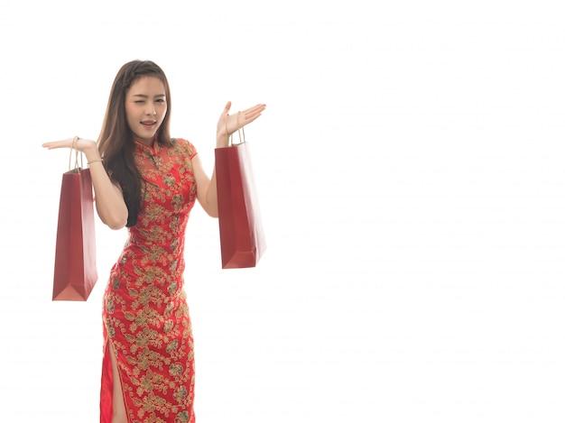 チャイナドレスを着て幸せなアジアの女性の肖像画は、白い背景で隔離赤い買い物袋、中国の新年のコンセプトでqipao笑顔の女性を保持します。コピースペースから解放されます。