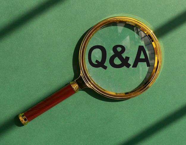 Акроним qna через увеличительное стекло на зеленом фоне вид сверху концепция экологических вопросов и ответов ...