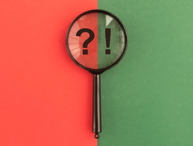 Qna concept magnifier with question and exclamation marks over red and green background