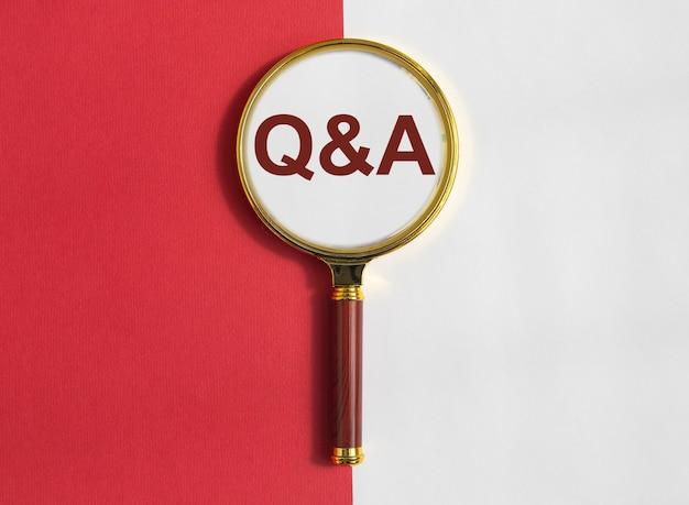 Надпись qna на красном и белом фоне через увеличительную линзу. акроним qa. концепция q. вопросы и ответы.