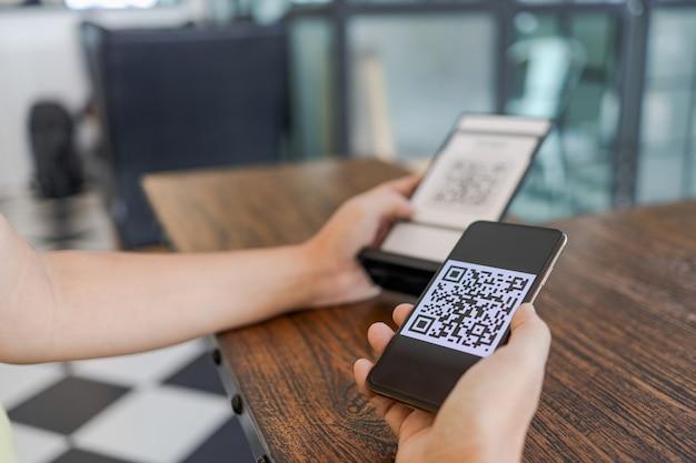 Qr코드 결제. 전자 지갑. 남자 스캐닝 태그는 돈 없이 디지털 지불을 생성합니다. qr 코드 온라인 쇼핑 현금 없는 지불 및 확인 기술 개념 스캐닝