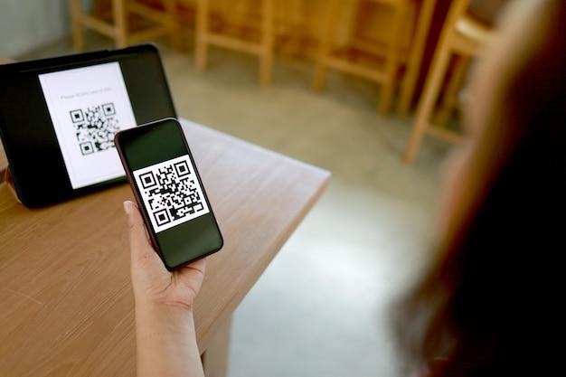 Qr 코드 결제. e 지갑. qr 코드 온라인 쇼핑 현금없는 기술 개념을 스캔하는 여자