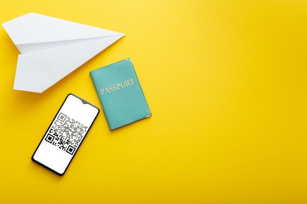 무료 여행 여름 방학을 위한 qr 코드 증거 음성 covid 19 pcr 테스트. 복사 공간이 있는 노란색 여름 배경의 스마트폰 화면 비행기 상단 보기에 있는 녹색 여권 인증서