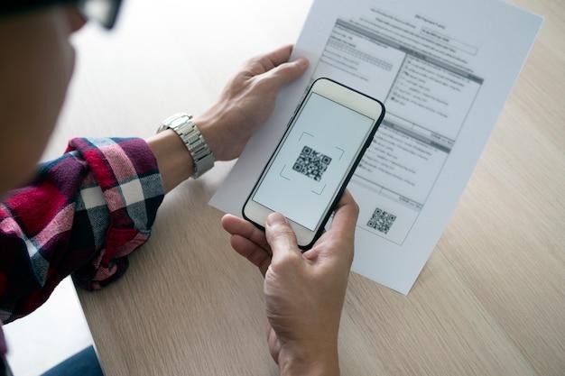 Человек использует смартфон для сканирования qr-кода, чтобы оплачивать ежемесячные счета по кредитным картам