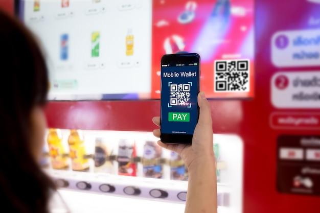 モバイルウォレットのコンセプト。女性の手がスマート自動販売機で携帯電話を介してqrコードをスキャン
