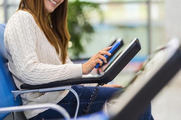 クローズアップ乗客の手を保持し、空港でメッセージ椅子のqrコードスキャナーマシンで携帯電話をスキャン