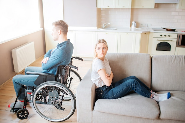 障害を持つ若い男が車椅子に座って、ウィンドウを見てください。口論とqu。特別なニーズを持つ男は、ガールフレンドと背中合わせに座っています。若い女性は彼を見てみてください。