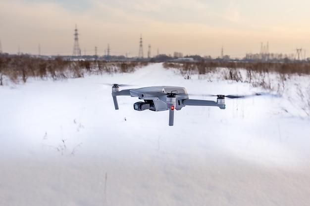 冬に雪原の上を飛ぶクワッドコプタードローン