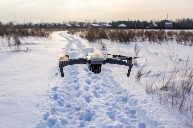 Quadcopter drone flying over a snowy field in winter on sunset
