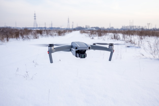 Quadcopter drone flying over a snowy field in winter.