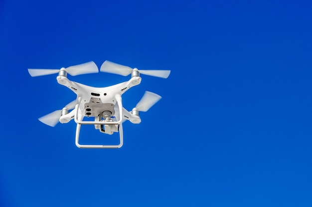 Quadcopter drone with the camera against the blue sky