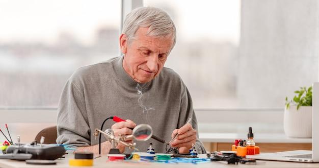 Процесс ремонта квадрокоптера с использованием различных профессиональных инструментов. человек, чинящий дрон