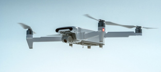 A quadrocopter drone with camera hangs in the air against a blue sky