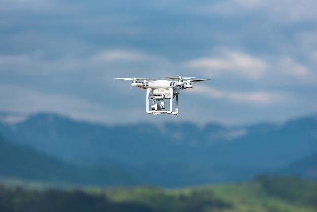 Квадрокоптер летит высоко над землей в природе