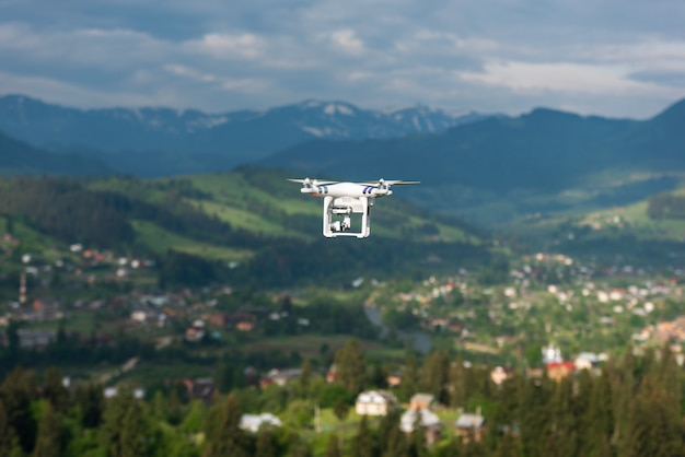 Quadrocopter flies high above the earth in nature