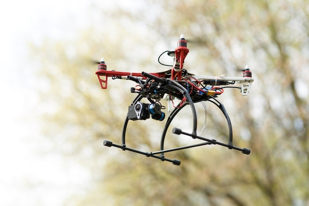 Квадрокоптер во время полета в лесу. концепция беспилотника.