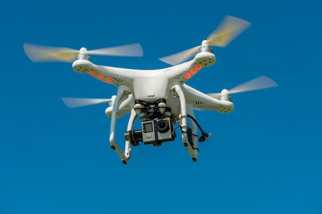 Квадрокоптер с камерой в полете на фоне голубого неба