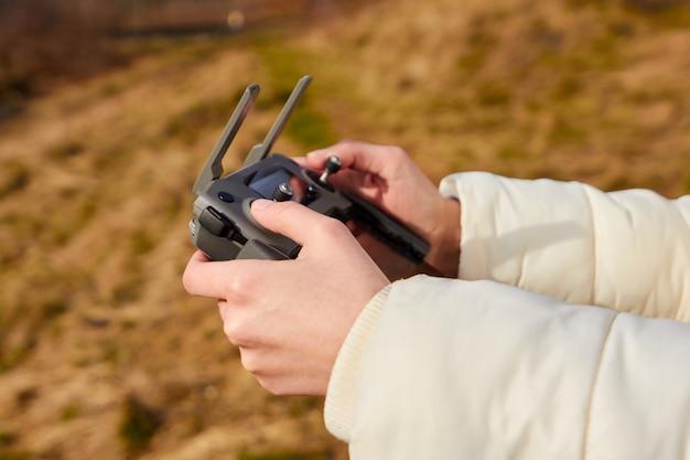 ドローンのリモートコントローラーを保持している梨花の手を閉じます。空中でのビデオ撮影。 quadrocopterフライトのコンセプト。