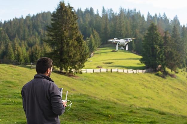 若い男が山の自然の空にquadrocopterを起動します