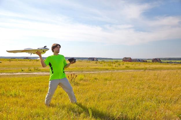 Quadrocopterのリモートコントロール、クローズアップ。男性の手で動くデバイスを制御するための送信機、ぼやけた自然の背景