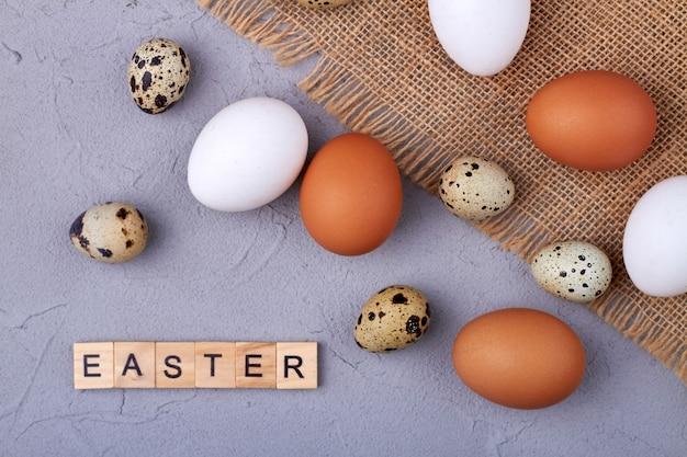 소박한 천에 메추라기 및 닭고기 달걀. 회색 표면에 부활절을위한 삶은 계란.