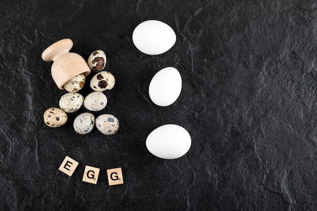 Перепелиные и куриные яйца на черной поверхности.