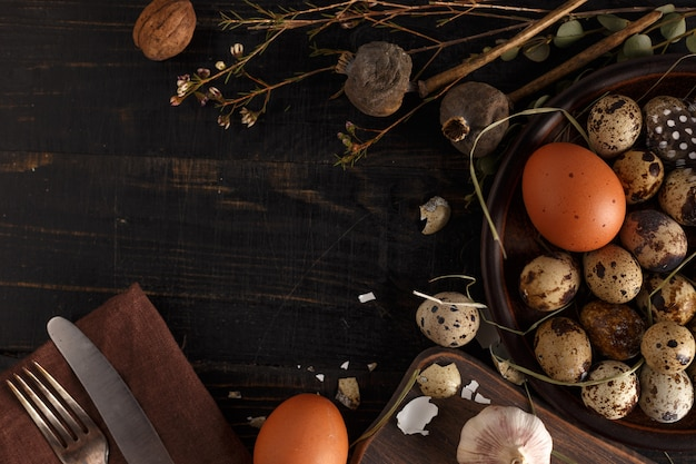 Quail and chicken eggs on a clay plate on a dark wooden surface.