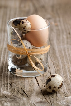 Quail and chicken eggs in glass