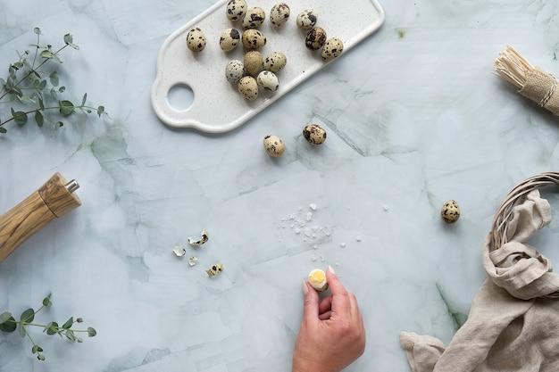 Перепелиные пасхальные яйца и натуральные весенние украшения и веточки эвкалипта. квартира лежала на мраморном столе.