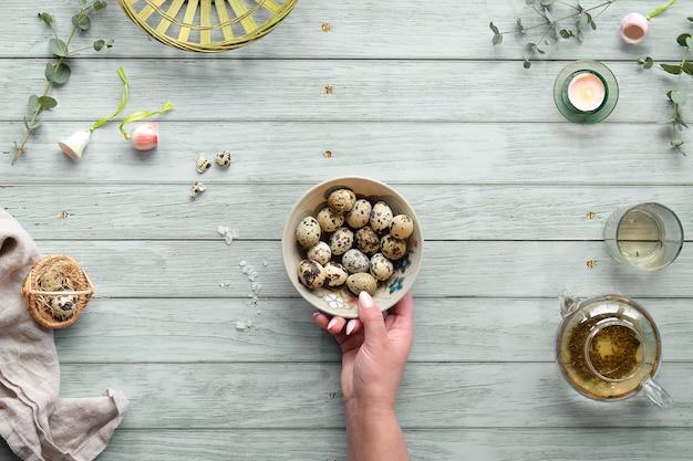 Перепелиные пасхальные яйца и натуральные весенние украшения и веточки эвкалипта на древесине зеленого цвета мяты.